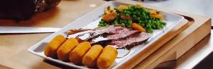 Gebakken rosbief van bij de slager met aardappelkroketten, erwten en wortelen
